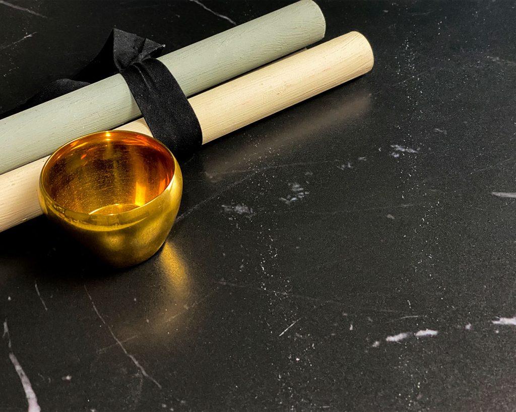 Copertina Marmi Pregiati Nero Ellenico con bicchiere in oro e 2 bacchette di legno per accedere alla pagina della serie