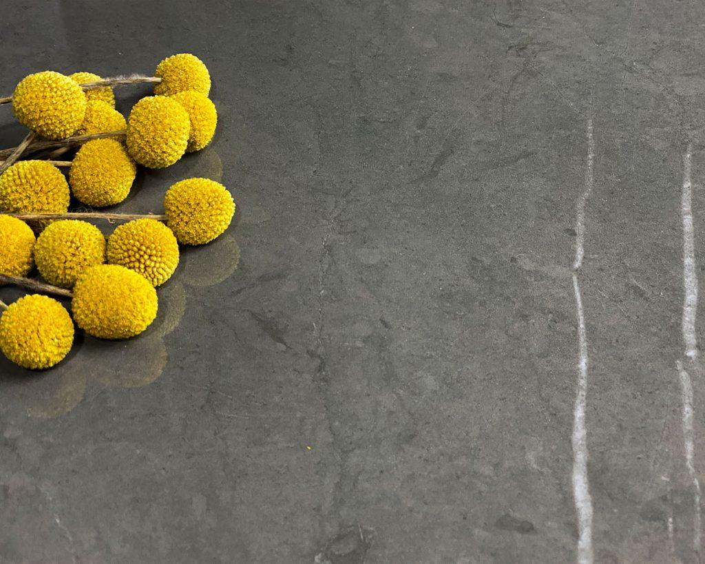 Copertina collezione Marmi Pregiati Pietra Grey con fiori finti gialli per accedere alla pagina della serie