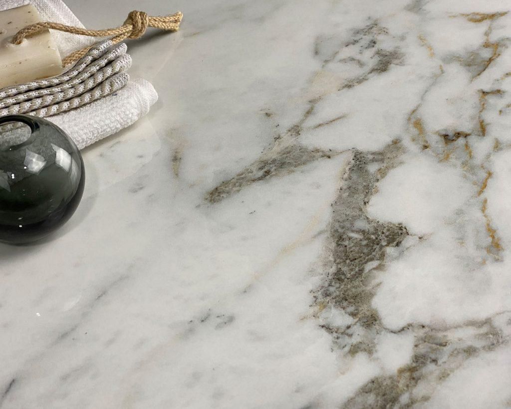 Copertina Marmi Pregiati Venato Reale con bicchiere di vetro nero, asciugamani bianchi piegati e una saponetta per accedere alla pagina della serie