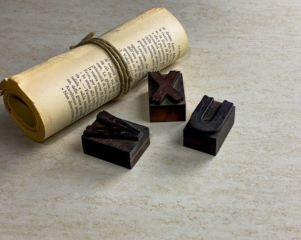 Copertina Marmi Pregiati Travertino con lettere tipografiche in legno e manoscritto per accedere alla pagina della serie